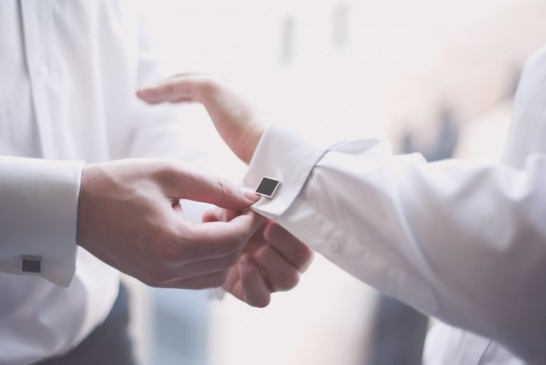 A groom gets help with his black square cufflinks at Citedines in Melbourne in wedding photography by Pause the Moment