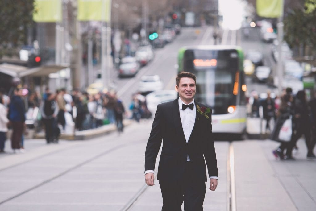 A groom crosses the road in front of a tram on his wedding day in Melbourne