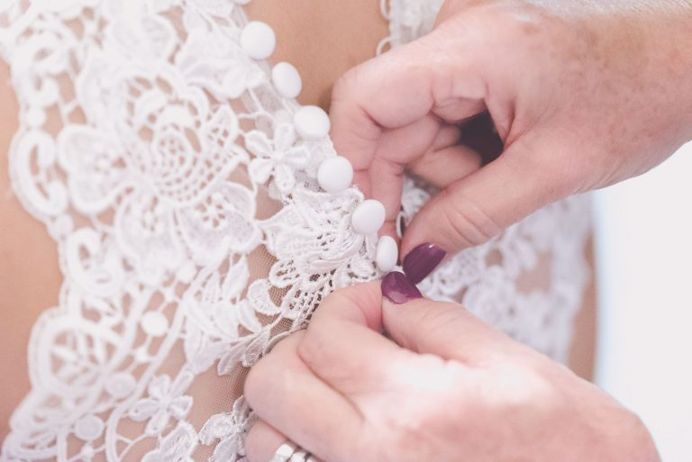 Detail of a wedding dress being buttoned up by pause the moment