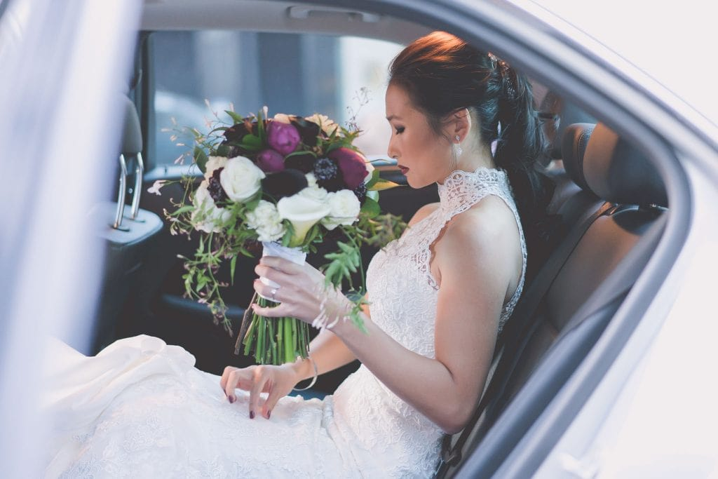 A beautiful bridesmaid with her Boquet adjusts her dress as she sits in her car before her Melbourne wedding. Photography by Pause Moment