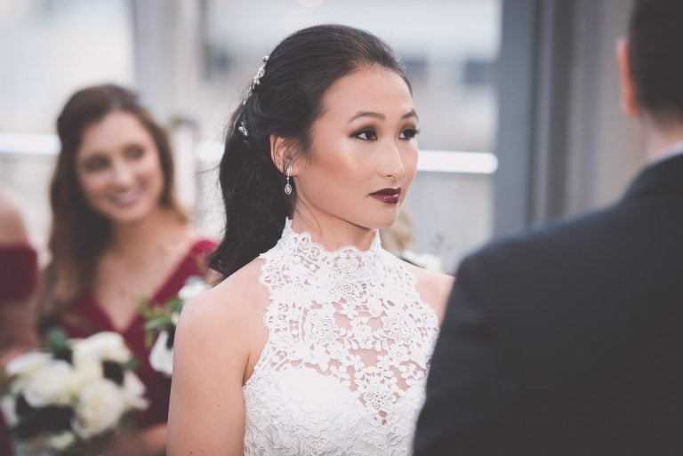 A beautiful bride looks at the celebrant with a bridesmaid in the background