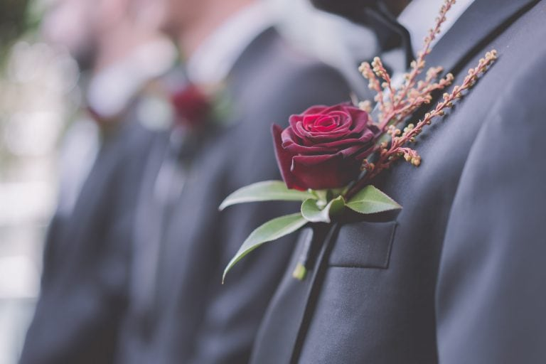 A beautiful red rose on the jacket of a groom at his wedding at alto GPO in Melbourne. Photography by Pause the Moment