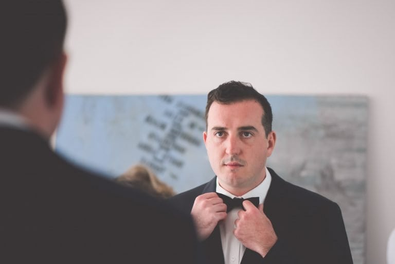 A nervous groom adjusts his tie before a Sandringham Beach wedding