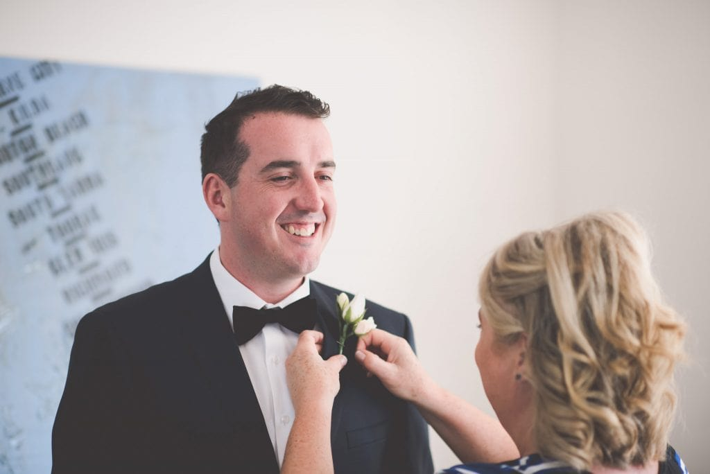 The groom's mother attaches his flower to his lapel