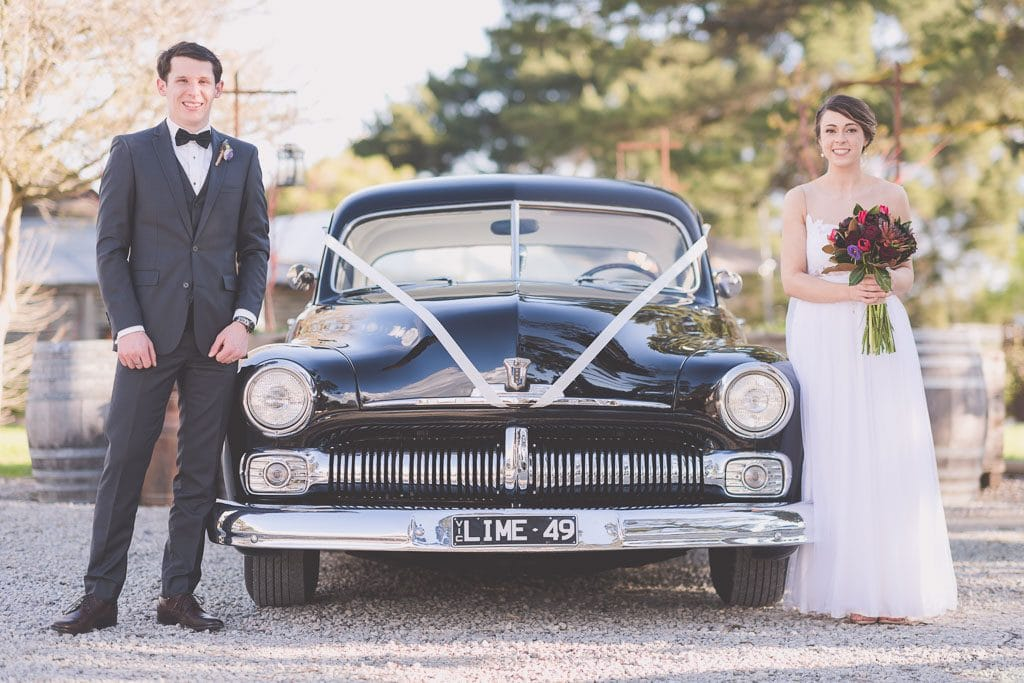 Bride and groom stand next to a black Ford that transported them to their Melbourne wedding.