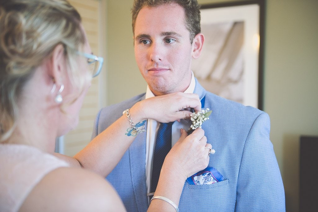 Mum puts a flower on her son's lapel