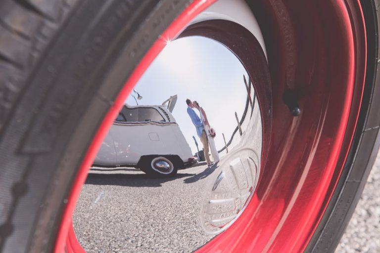 Bride and groom reflected in the hub cap of a VW beetle.