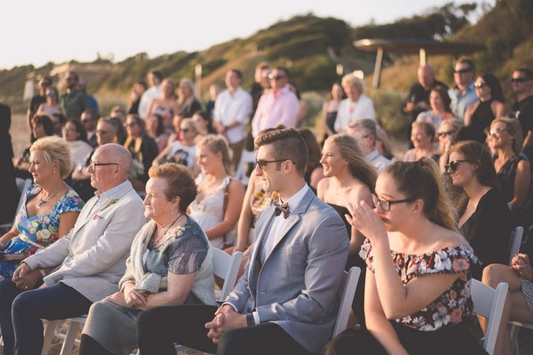 Family and friends watch a wedding on the beach in Mentone