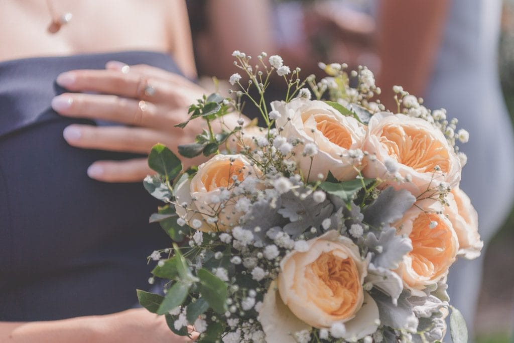 A closeup of an orange bridesmaid's bouquet at Stillwater Crittenden Estate at their Mornington Peninsula wedding photography.