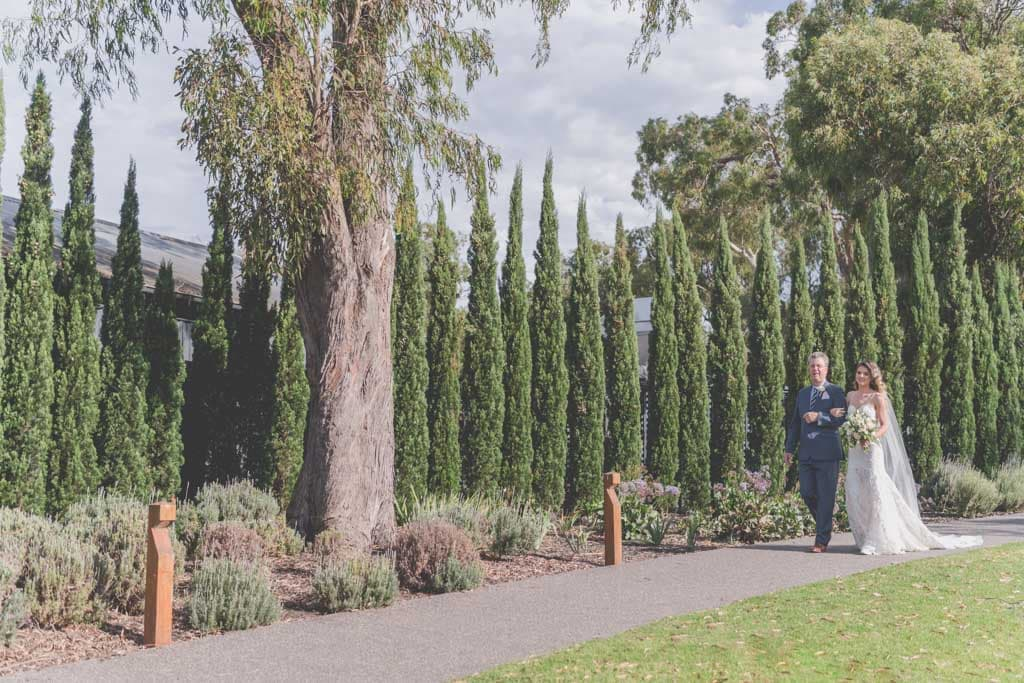 The bride is walked down the path to her groom by her father at Stillwater Crittenden Estate during their Mornington Peninsula wedding photography.