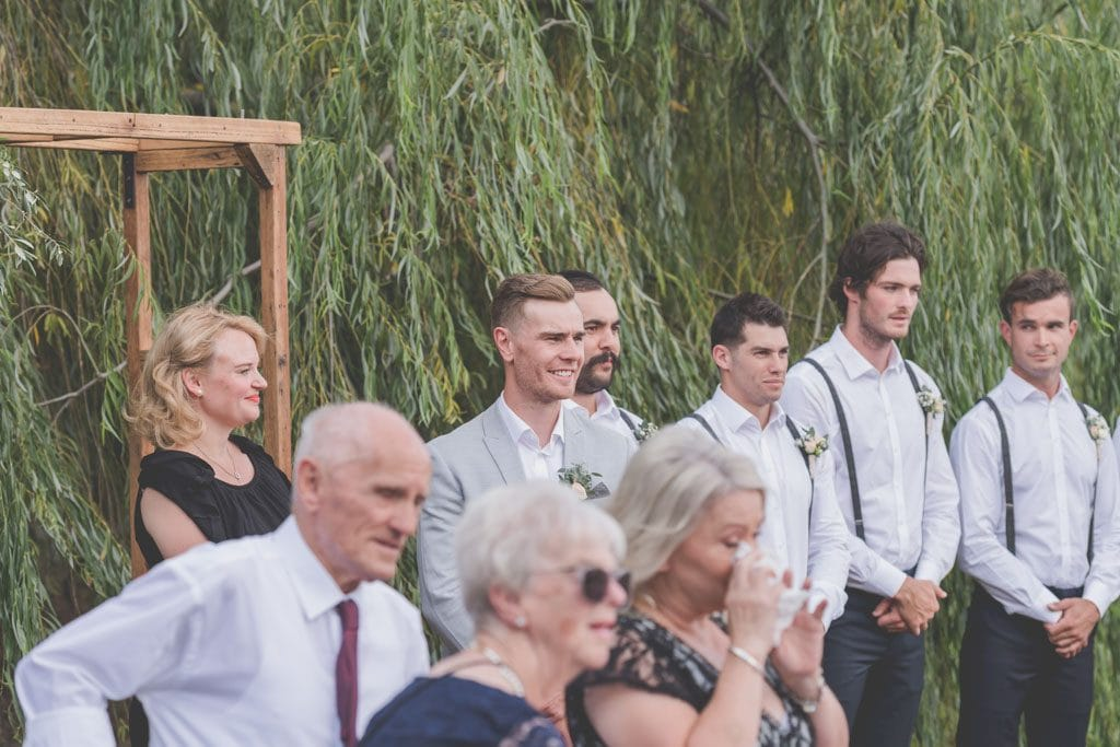 The groom looks happily down the aisle at Stillwater Crittenden Estate at their Mornington Peninsula wedding photography.