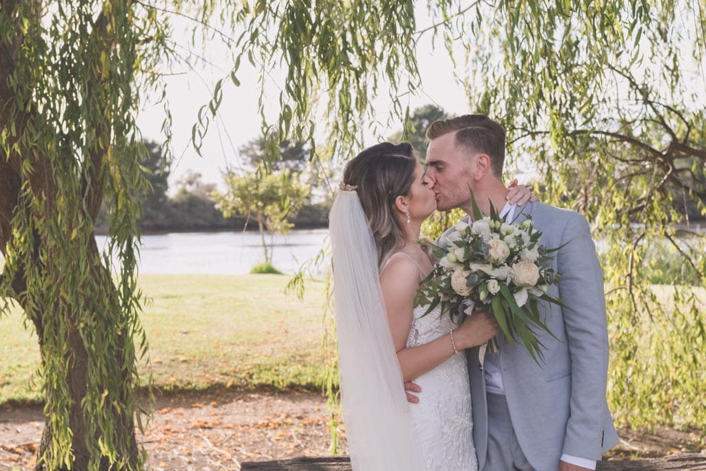The couple kiss by the lake at their Mornington Peninsula wedding photography.