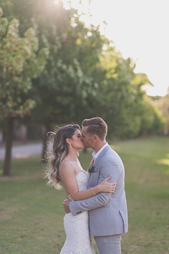 A sunset kiss by trees during Mornington Peninsula wedding photography.