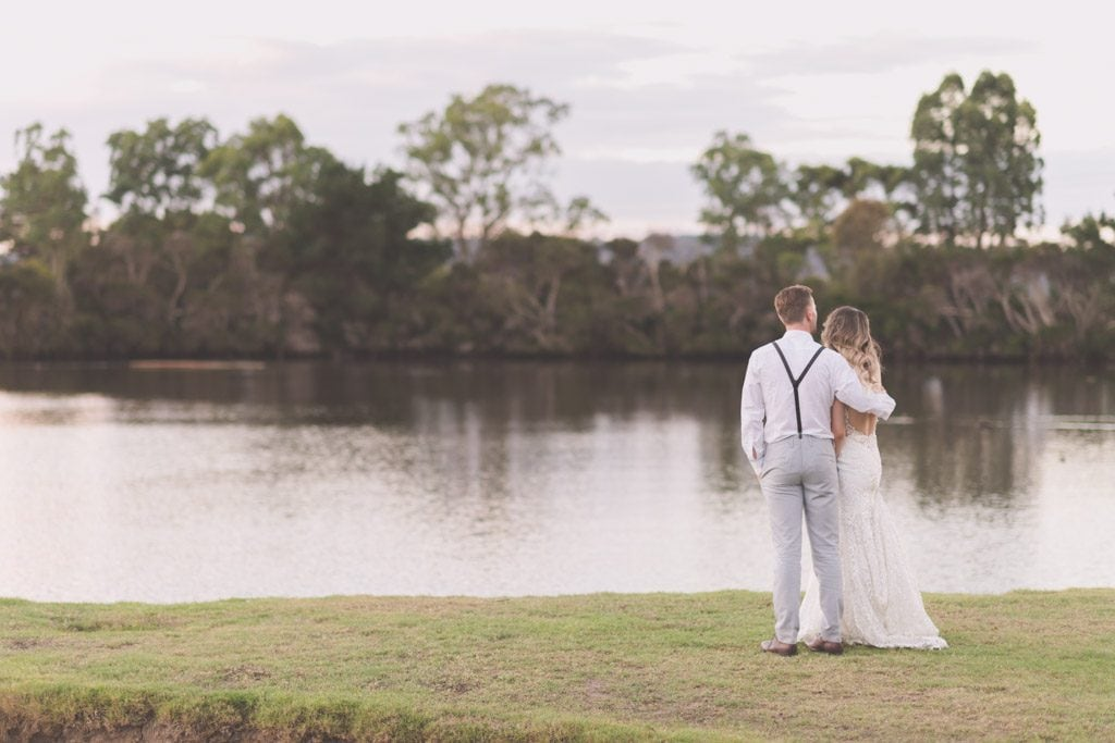The backs of a bride and groom as they look out over a lake during their Mornington Peninsula wedding photography.