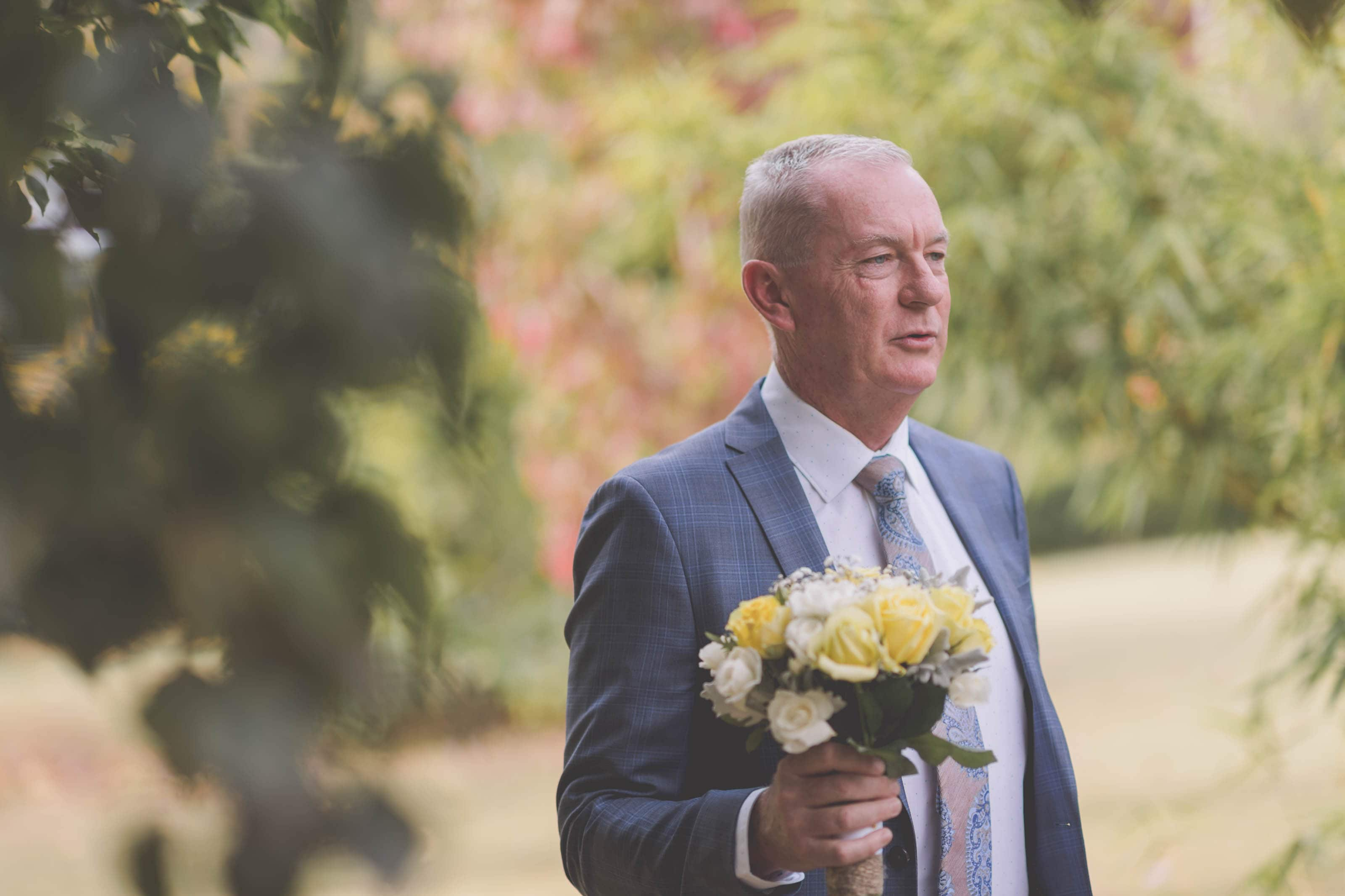 Wedding Photography Melbourne by Pause The Moment - Bride's dad holds her flowers before her Melbourne wedding - Paringa Estate Wedding Photographer