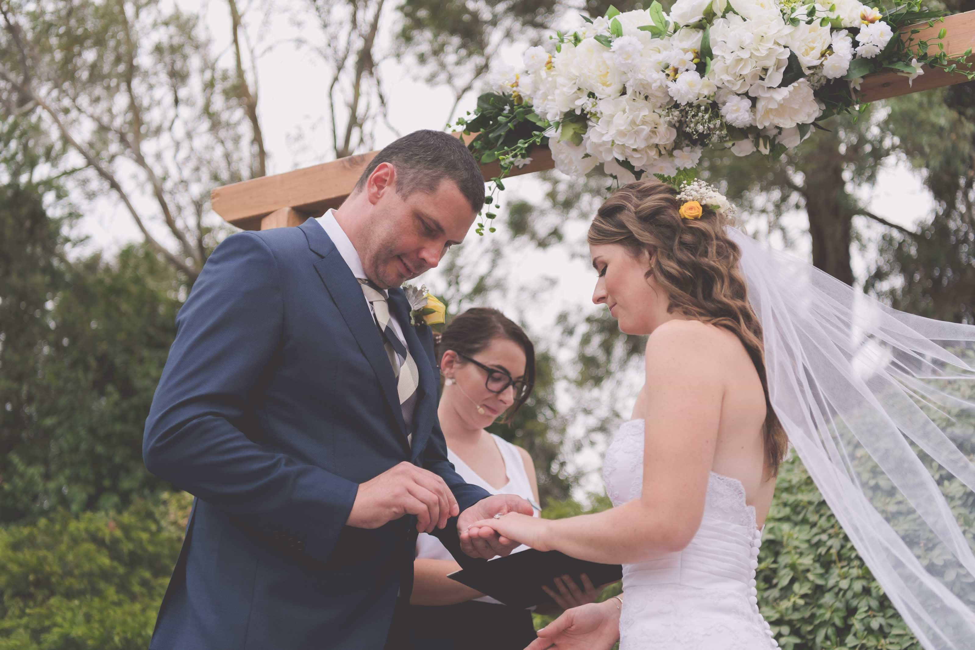 Wedding Photography Melbourne by Pause The Moment - Groom puts his ring on his bride at a Melbourne wedding - Paringa Estate Wedding Photographer