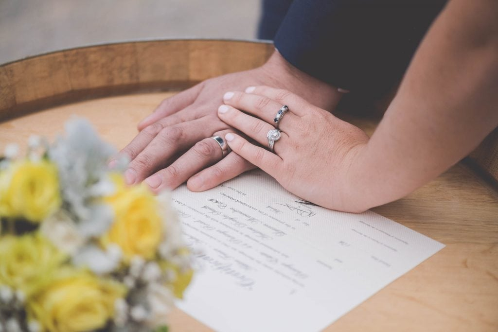 Wedding Photography Melbourne by Pause The Moment - Hands, rings and a wedding certificate on a rustic barrel at a Melbourne wedding - Paringa Estate Wedding Photographer