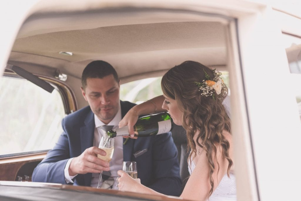 Wedding Photography Melbourne by Pause The Moment - Pouring champagne in the back of a Roll's Royce - Paringa Estate Wedding Photographer
