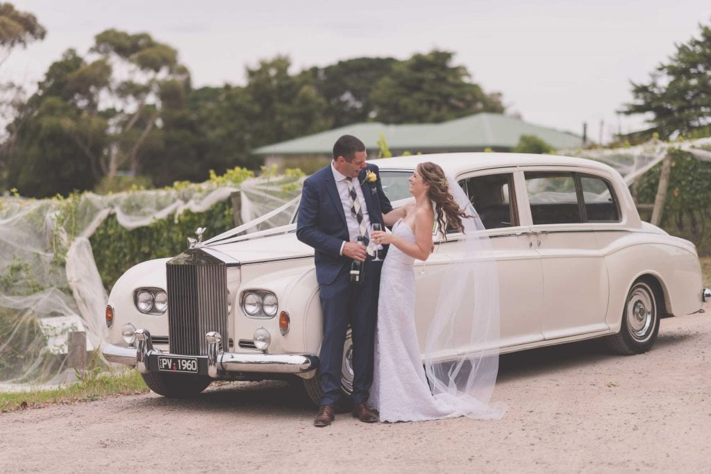 Wedding Photography Melbourne by Pause The Moment - A couple on their wedding day laugh in front of a Roll's Royce - Paringa Estate Wedding Photographer