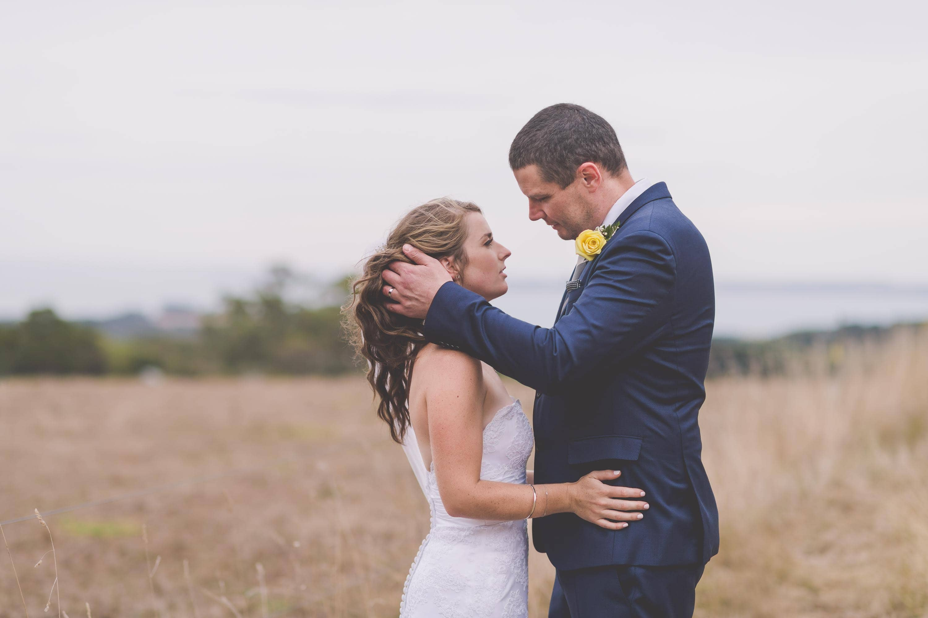Andrew and Lauren embrace in the fields at Paringa Estate