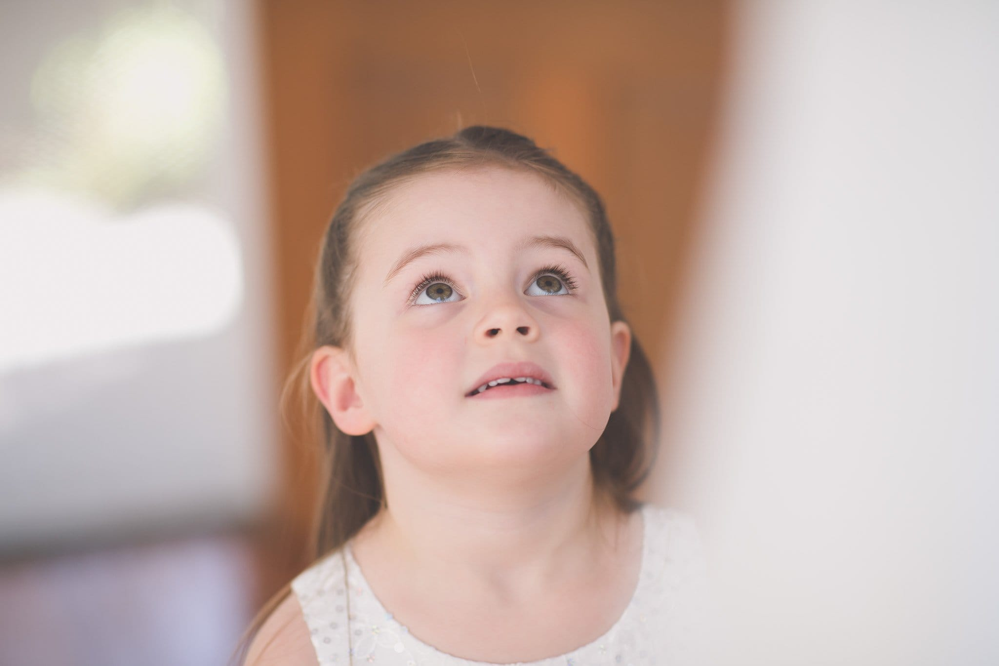 Melbourne wedding photography of a flower girl's face looking up at a wedding dress
