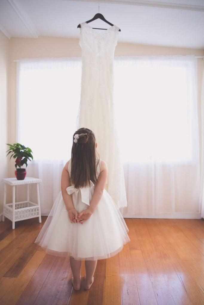 Melbourne wedding photography of a flower girl looking up at a wedding dress