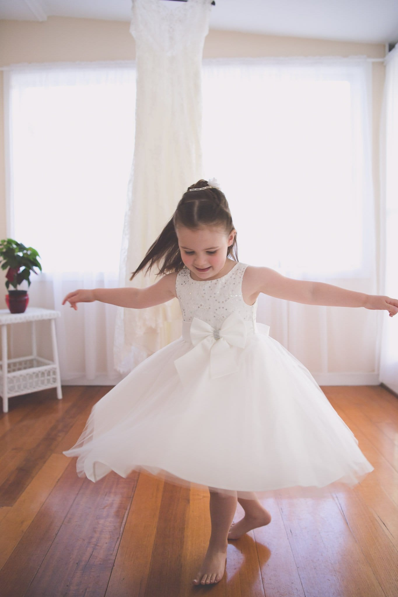 Melbourne wedding photography of a flower girl twirling in front of a wedding dress