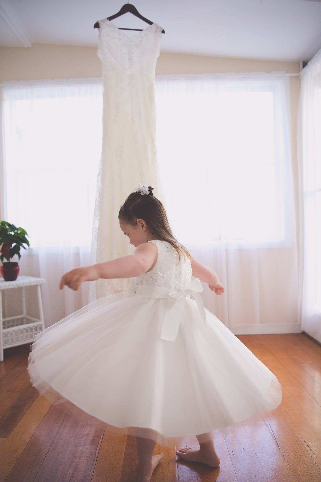 Melbourne wedding photography of a flower girl dancing in front of a wedding dress