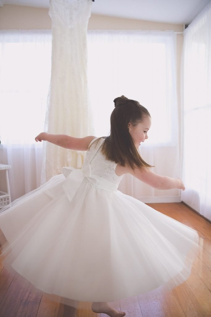 Melbourne wedding photography of a flower girl swirling in front of a wedding dress