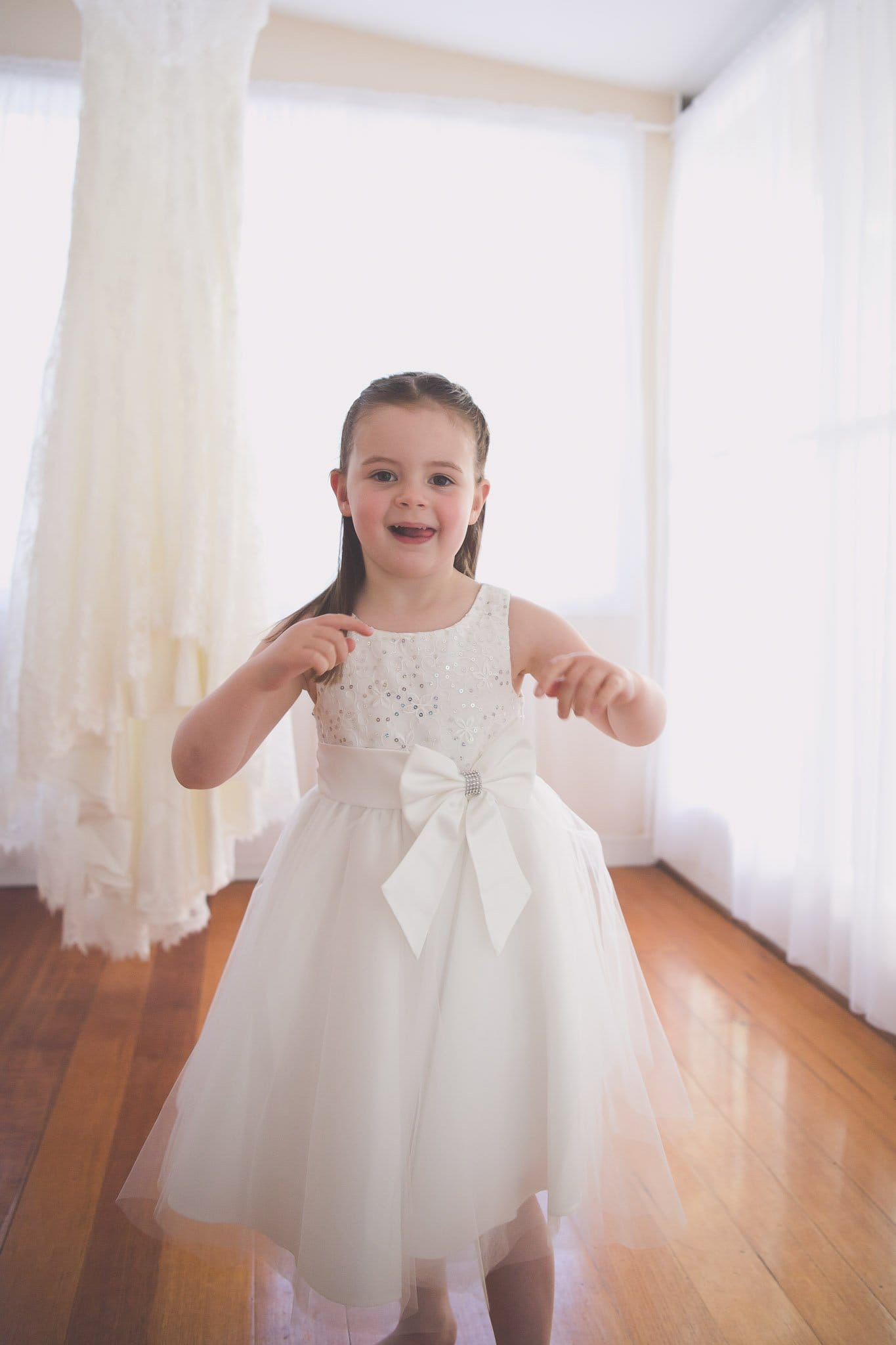 Melbourne wedding photography of a flower girl smiling in front of a wedding dress