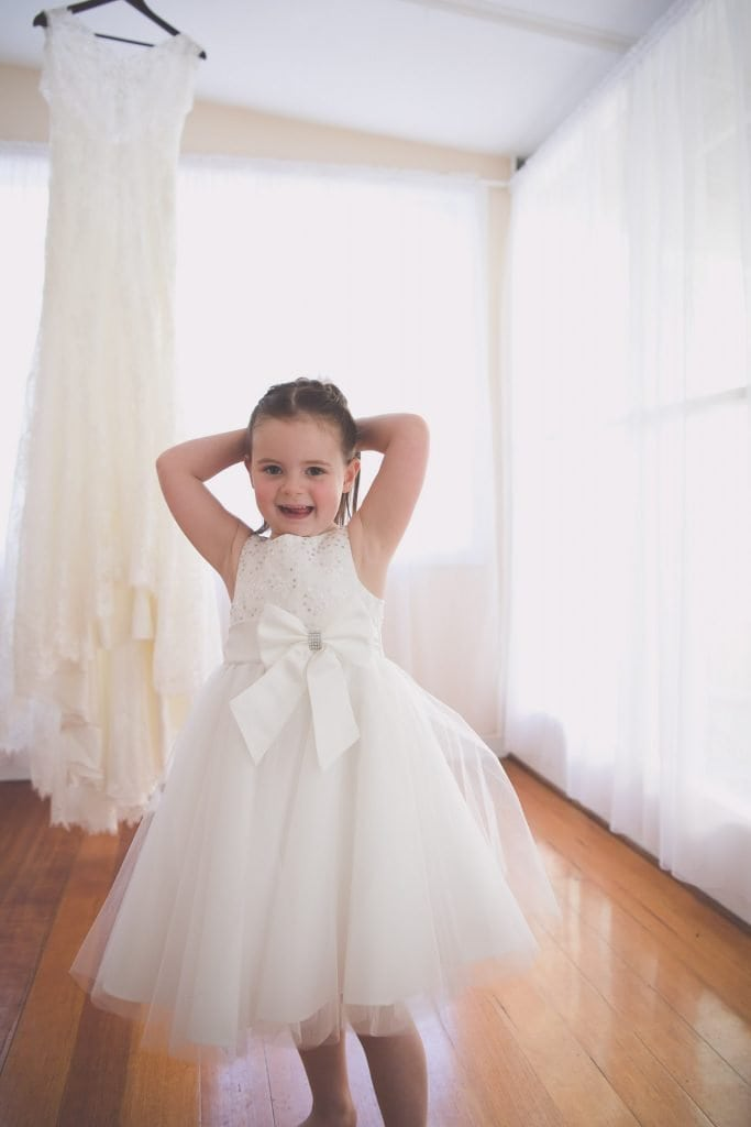 Melbourne wedding photography of a flower girl looking shy in front of a wedding dress