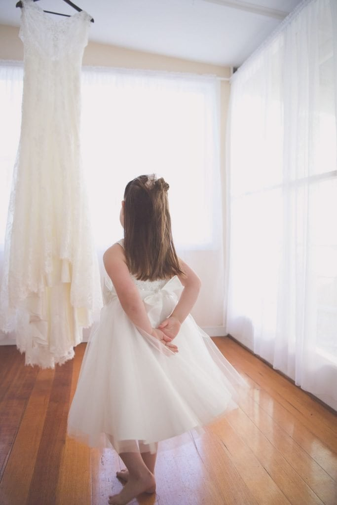 Melbourne wedding photography of a flower girl looking watching a wedding dress