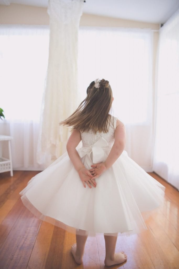 Melbourne wedding photography of a flower girl swishing her skirt in front of a wedding dress