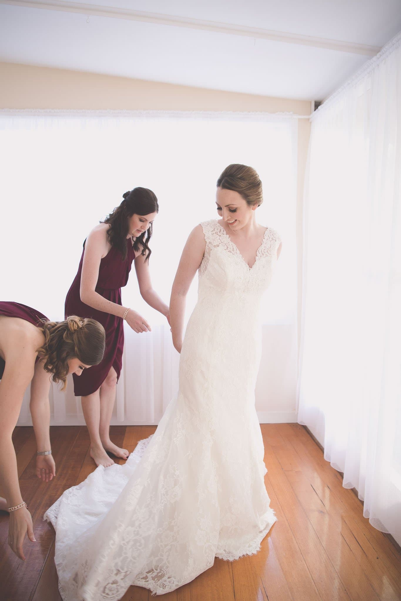Melbourne wedding photography of the bride being helped into her dress