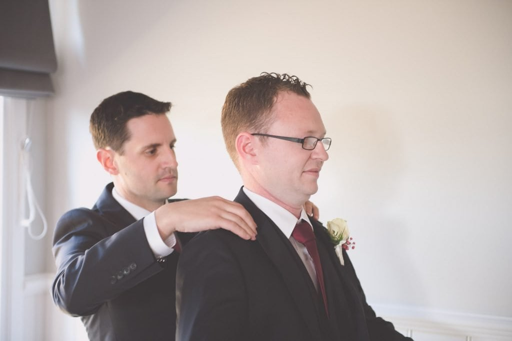 Melbourne wedding photography of the groom getting help with his jacket from a groomsman