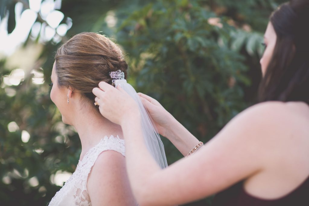 Melbourne wedding photography of the bride having her veil affixed