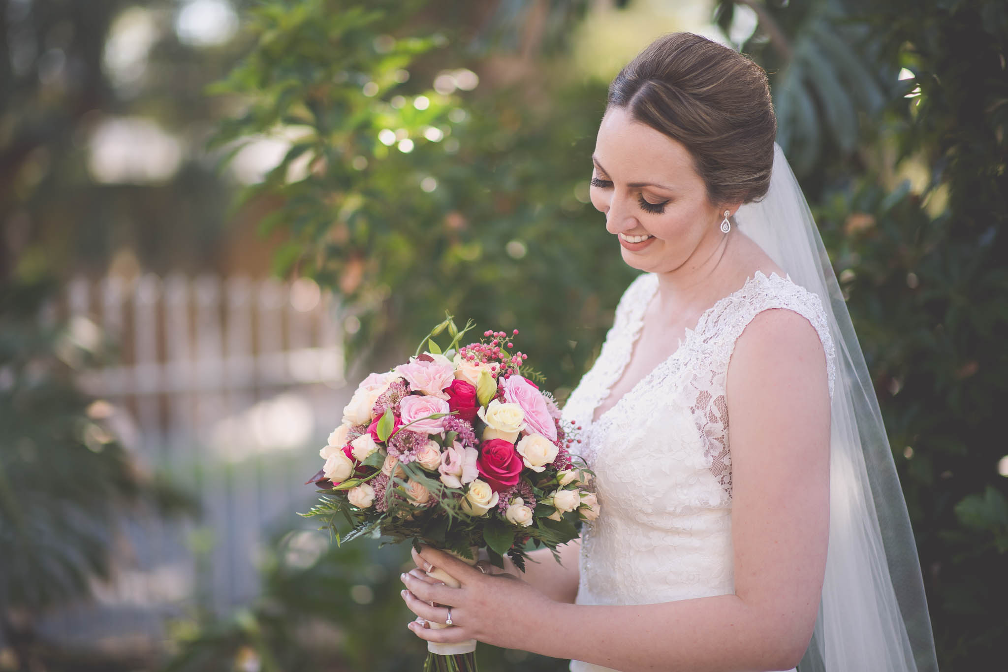Melbourne wedding photography of the bride smiling at her flowers in the bouquet