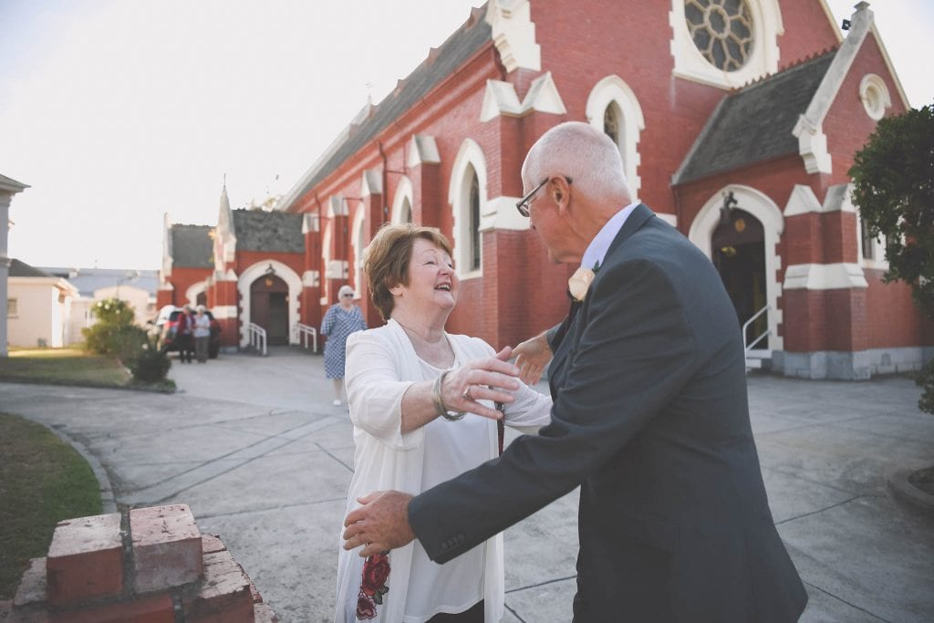 A couple embrace outside a Melbourne wedding. Photography by Pause The Moment