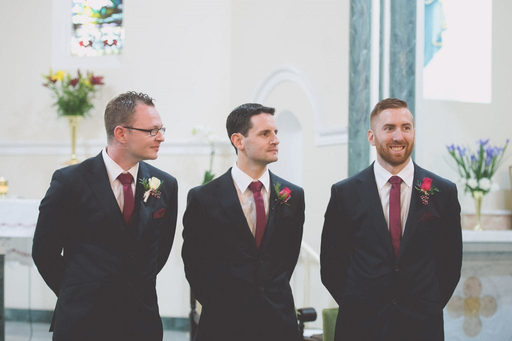 A groom and his groomsmen stand and wait inside a Melbourne Church for their wedding photography.