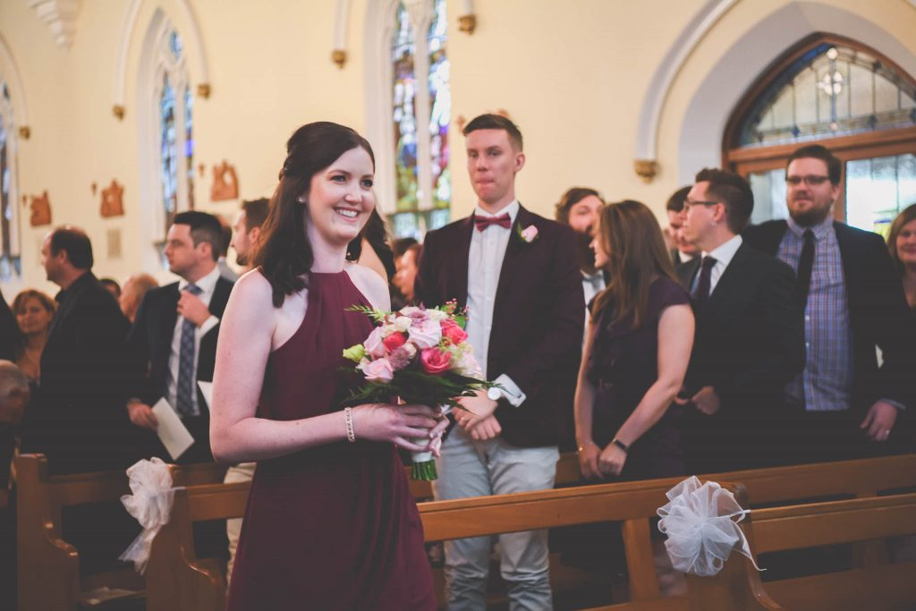 Beautiful Melbourne wedding photography of a bridesmaid walking down the aisle at a church.