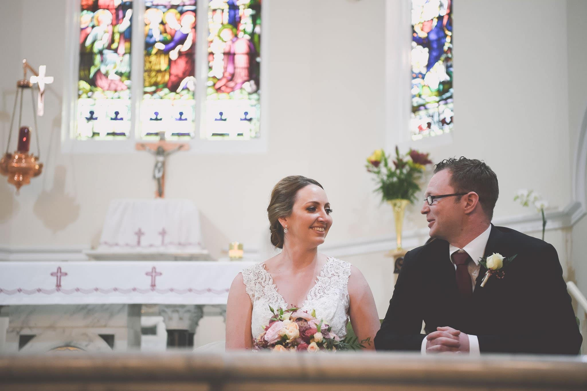 Candid Melbourne wedding photography of a bride and groom share a smile at the altar on their wedding day.