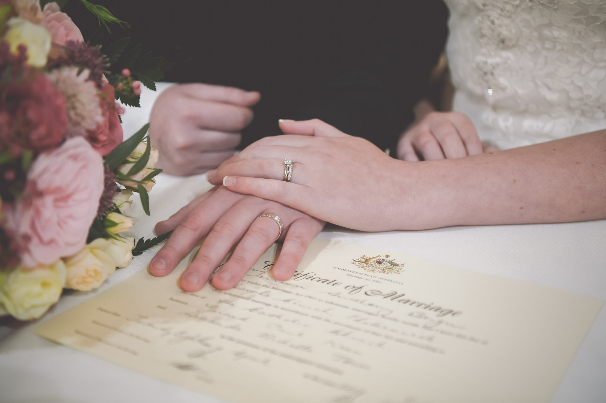 Beautiful wedding photography of a bride and groom's hands resting on their wedding certificate