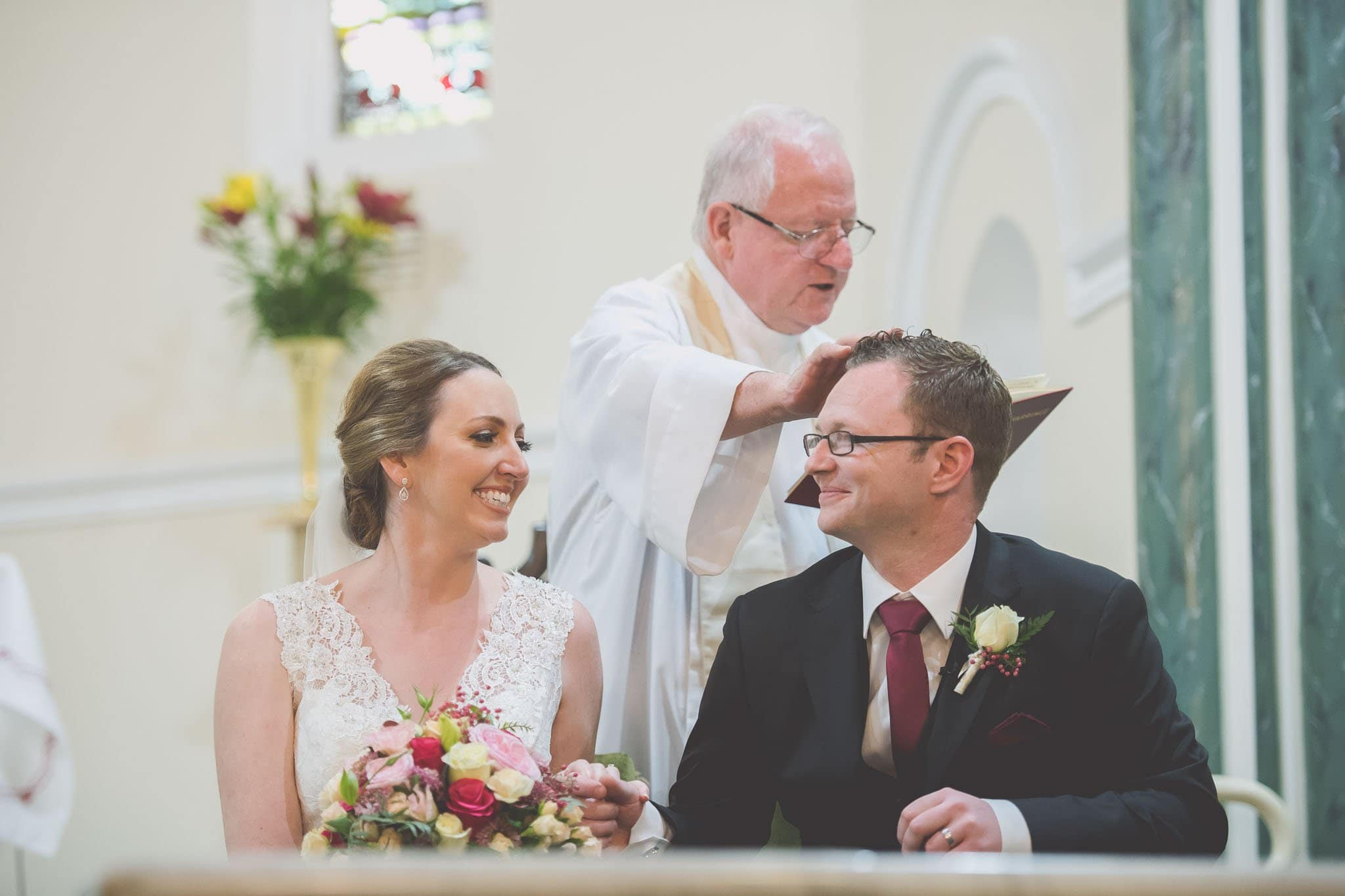 Wedding photography of a priest blessing the groom and bride at a Melbourne wedding.