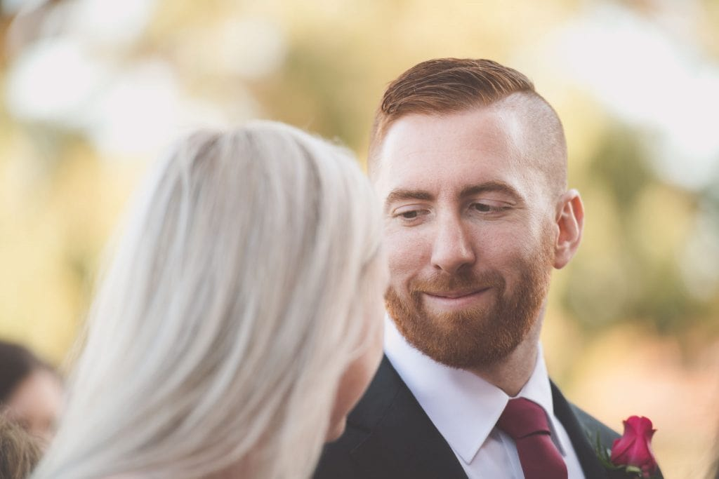 Beautiful wedding photography of a groomsman looking at his partner after a wedding in Melbourne.