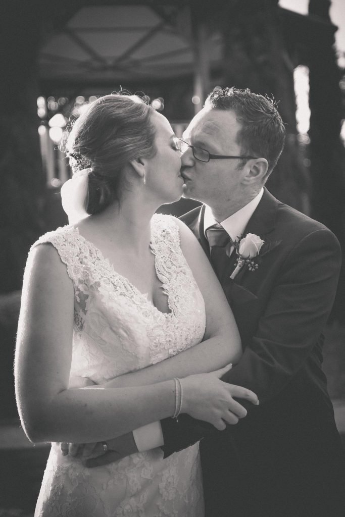 Gorgeous black and white wedding photography of a couple kissing in a park after their Melbourne wedding.