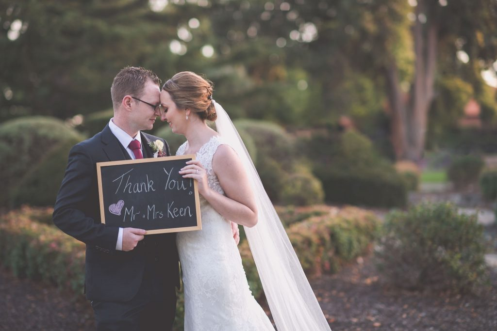 A beautiful Melbourne wedding photo of a bride and groom holding up their thank you sign. Captured by Melbourne wedding photographer Pause The Moment