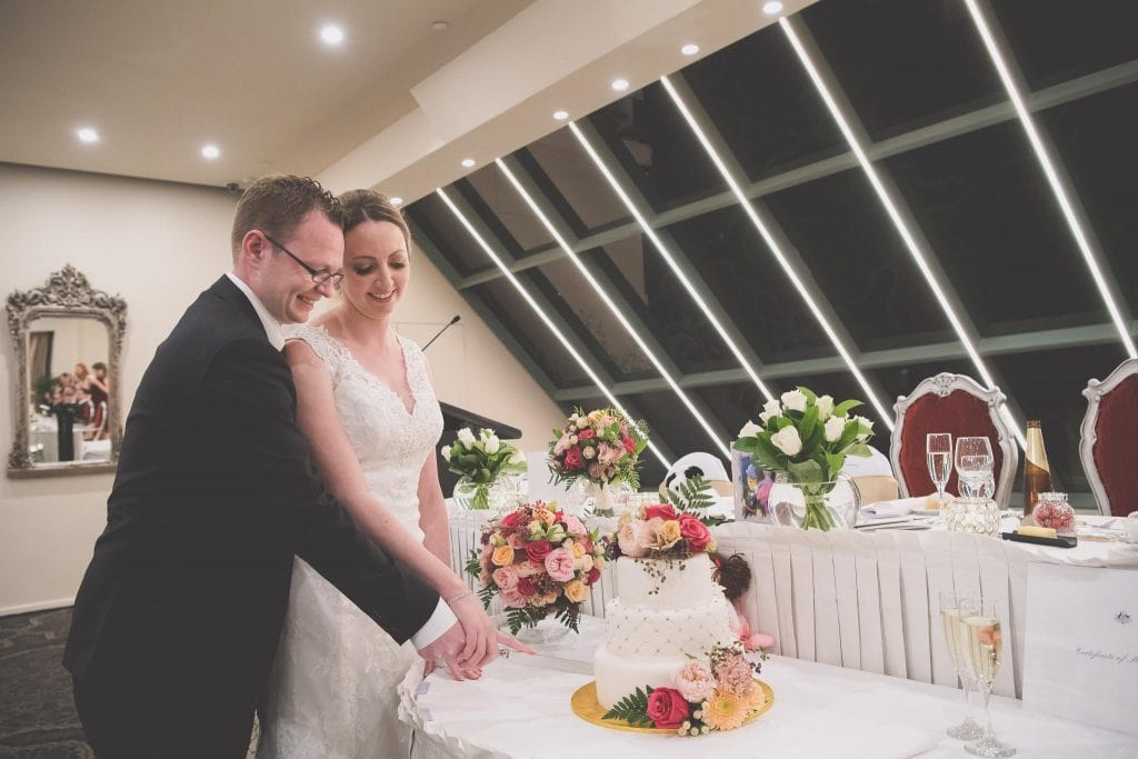 Gorgeous wedding photography of a bride and groom cutting their cake. Image captured by Melbourne wedding photographer Pause The Moment