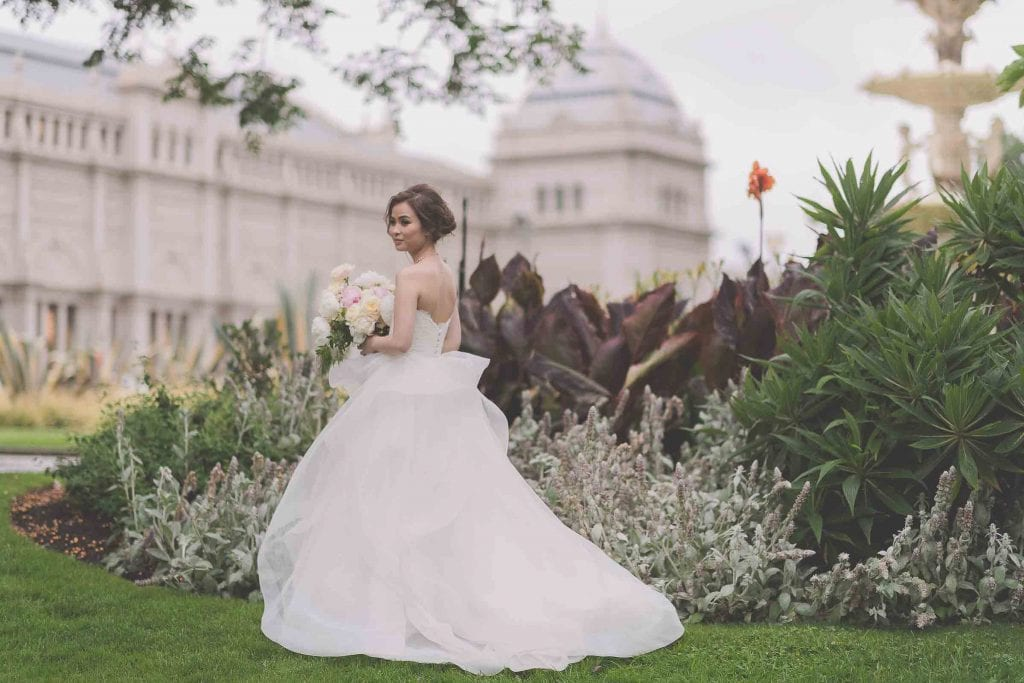 Melbourne wedding photography in Carlton Gardens of the bride looking over her shoulder