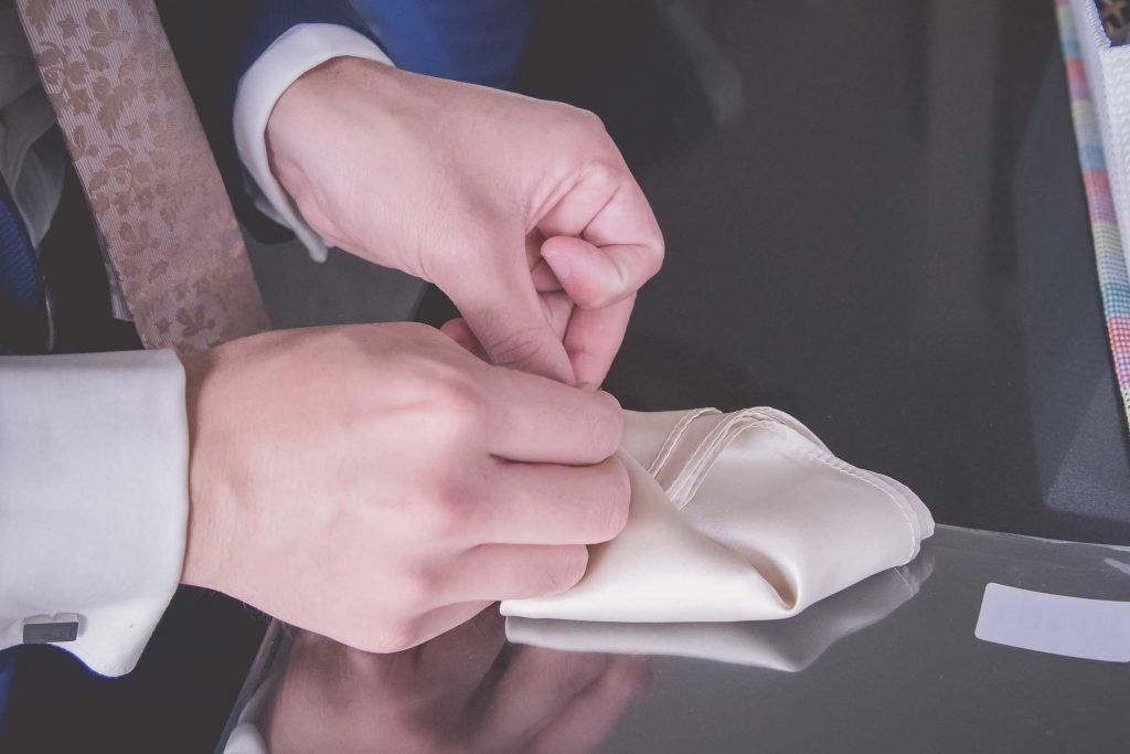 Melbourne wedding photography of the pocket square being folded