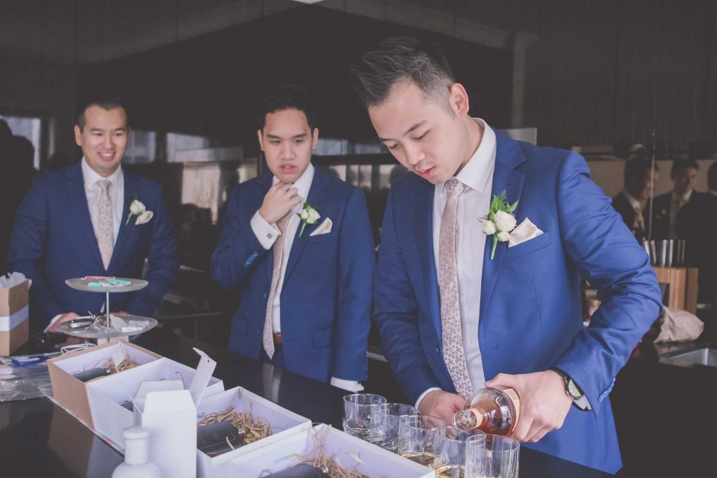 Melbourne wedding photography of a groomsman pouring whiskey